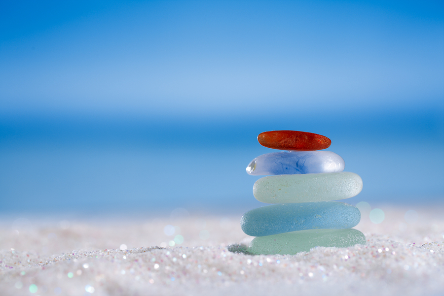 sea glass seaglass stone on glitter sand with ocean , beach